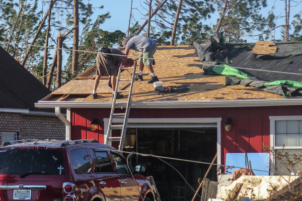 Lance Erwin works with a neighbor in Mexico Beach, Fla., to repair parts of his roof after it was blown off by Hurricane Michael. Rules are looser in the Pandhandle, allowing construction that couldn't stand up to the storm's 155 mph winds.