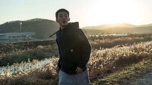 Jong-su (Yoo Ah-in) goes for a run in <em>Burning</em>.