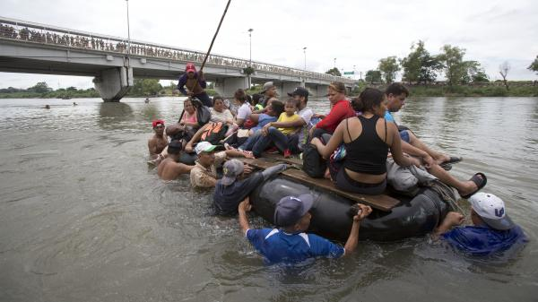 A group of Central American migrants cross the Suchiate River aboard a raft, on the the border between Guatemala and Mexico, in Ciudad Hidalgo, Mexico on Saturday. After Mexican authorities slowed access through the border bridge to a crawl, hundreds of migrants are boarding the rafts or wading across the river and crossing into Mexico illegally.