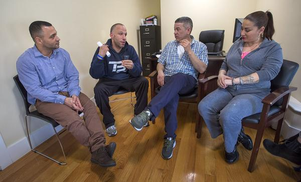 From left to right: Felito Diaz, Julio Cesar Santiago, Richard Lopez and Irma Bermudez speak at Casa Esperanza, a collection of day treatment, residential programs and transitional housing in Roxbury. (Jesse Costa/WBUR)