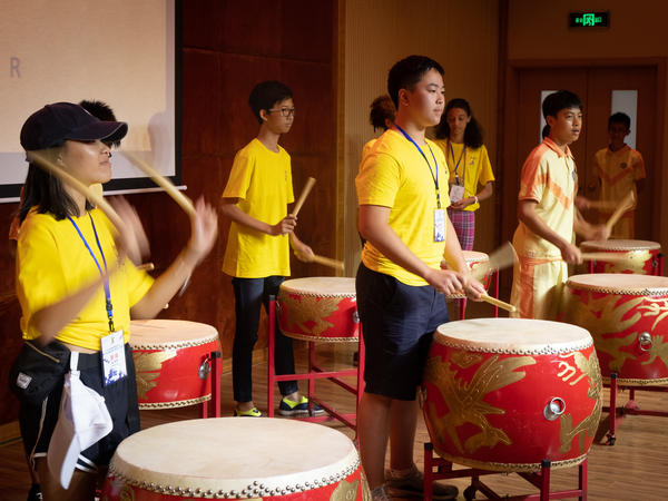 Students from the U.S. and Indonesia play drums in a music class in Taishan.