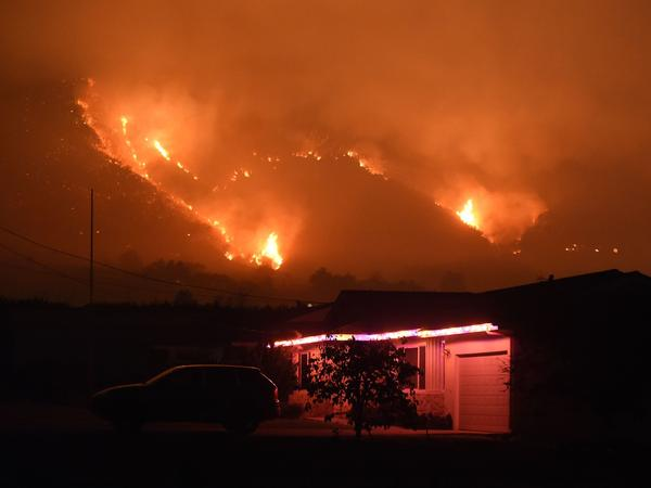 Flames from the Thomas Fire burn in the hills above Carpinteria, California, Dec. 11, 2017.