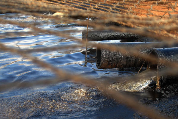 Dirty water from the oil wells flows through oil-caked pipes into a settling pit where trucks vacuum off the oil. A net covers the pit to keep out birds and other wildlife. Streams of this wastewater flow through the reservation and join natural creeks and rivers.