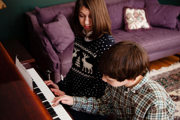 "Samantha watches her brother Nicholas play piano. Their mother says that a new customized voice created by researcher Rupal Patel from a young Samantha's voice sample is happy and has a sweetly familiar quality. ""My son — my son Nicholas — I could hear some of his voice in it,"" she says."