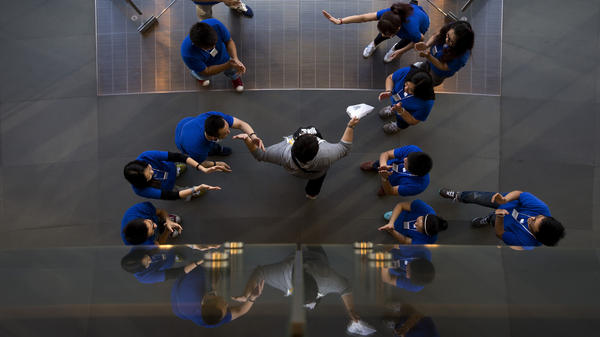 Apple says it has sold 9 million iPhone 5s and 5c models since their launch on Friday. Here, staff members at an Apple retail store in Beijing cheer a customer after he bought a new iPhone.