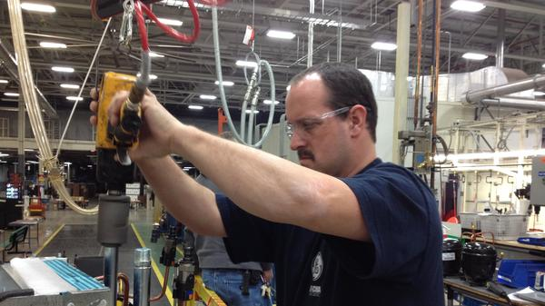 Paul Gibson works on the Geo-Spring hybrid water heater at General Electric's Louisville, Ky., plant. For many years, GE outsourced manufacturing of the water heater to a company in China. But in 2009, it decided to bring production back to the U.S.