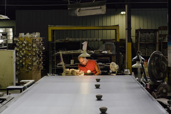 Hand liner Kevin Manypenny sends finished items down a conveyor belt to the next step on the production line. While the work he does can be automated, it's often faster to hand him the slip of the paper with the order than to reconfigure a machine.