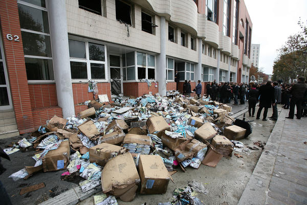 "Fire-damaged objects are scattered outside <em>Charlie Hebdo</em> offices following the firebombing in 2011. The attack, which completely destroyed the offices, came a day after the magazine featured a caricature of the Prophet Muhammad on its cover and named him ""editor-in-chief."""