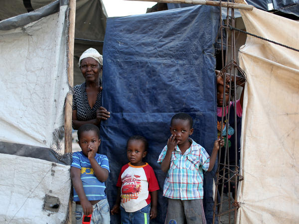 Members of a family look out from behind the tarp that serves as the front door to their home. The structure was built five years ago over the land where their home stood before the 2010 earthquake. At one point, about 1.5 million people lived in tents across Haiti. Now about 80,000 people live in these structures.