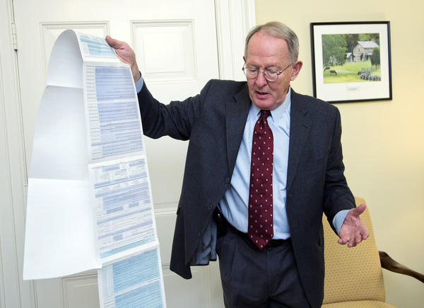 Sen. Lamar Alexander, R-Tenn., holds the Free Application for Federal Student Aid, or FAFSA. Alexander is pushing to shorten the 108-question form to just two questions.