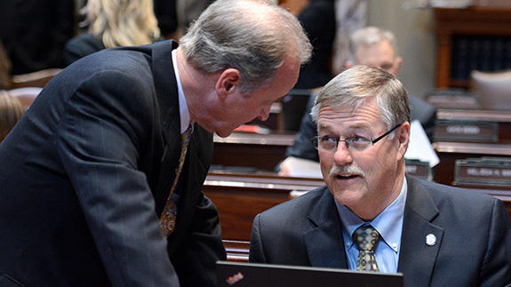 "State Sens. Warren Limmer (left) and Bill Ingebrigtsen talk in the Senate chamber. Limmer said he has been scolded for looking at his colleagues during debate before, and had ""to beg forgiveness to the Senate president."""