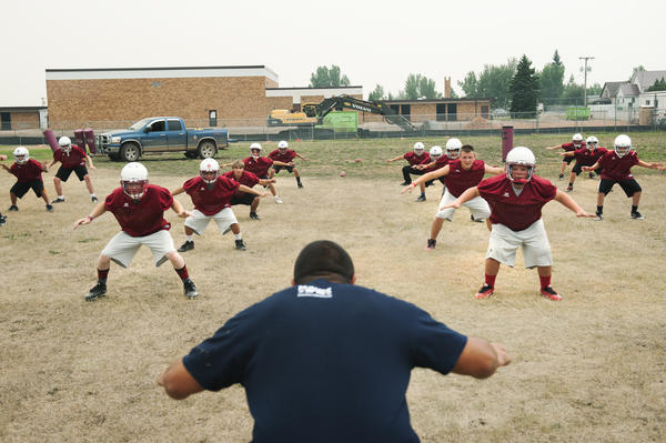 Alexander High School teacher and football team defensive coordinator Mike Rizzo (center) leads the high school and junior high teams through warm-up stretches at a practice in August. Most of the members of the team, which plays in a six-man division, have never played organized football before.