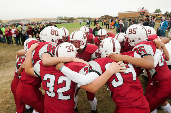 The Alexander Comets huddle and chant before taking the field for the first time since 1987.