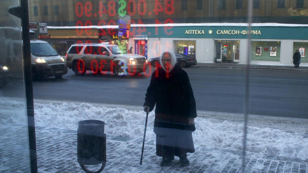 An elderly Russian woman stands at a bus stop with exchange rates reflecting in glass in Moscow on Jan. 21. As the ruble declines and oil prices continue to slide, pensioners are among the hardest hit.