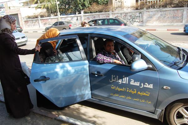 Students enter a car with instructor Abdel Nasser el-Bobbo in the passenger seat. To get around Hamas' recent crackdown on male instructors who are alone with female students, schools ask students to ride along with other learners.