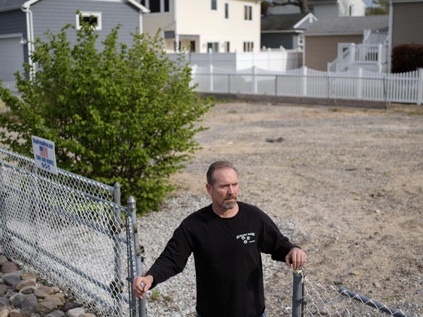 Doug Quinn stands on the empty lot where his house used to be.