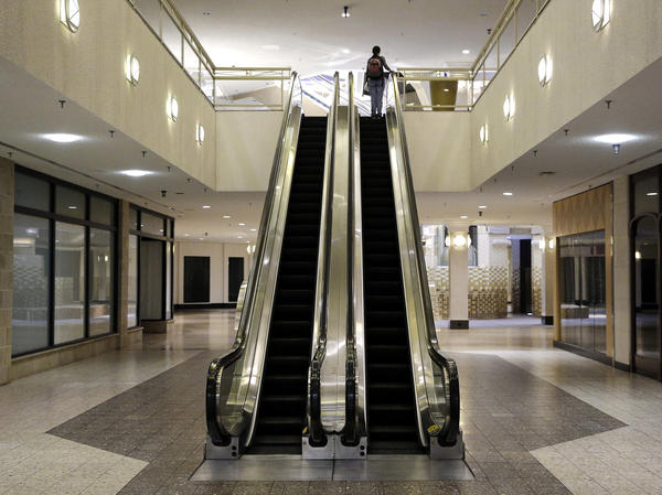 A woman rides an escalator past closed storefronts inside the largely empty White Flint Mall, in Bethesda, Md., in 2014. The mall closed last year.