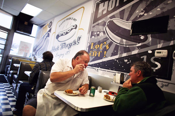 Harlan eats a Coney with a customer.