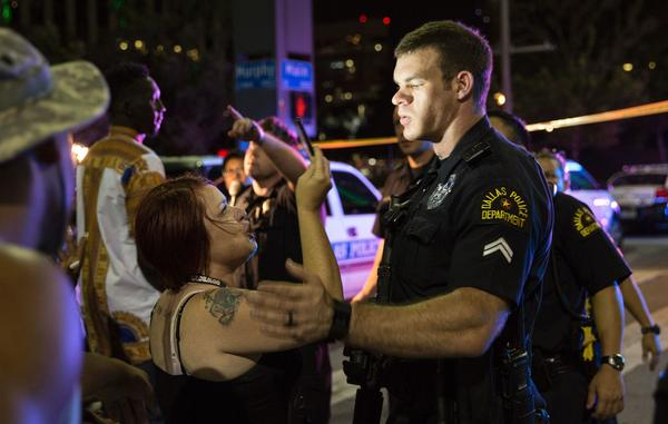 A woman holds a cellphone up to a police officer as an attempt is made to calm the crowd after an arrest is made following the sniper shooting in Dallas on Thursday.