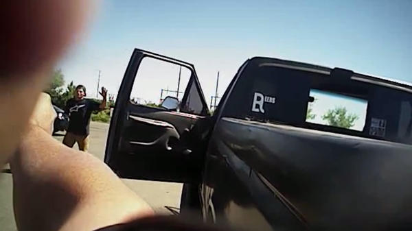 In this image made from a June 25 police body-camera video released by Fresno Police Department, a police officer points a gun at Dylan Noble in Fresno, Calif.