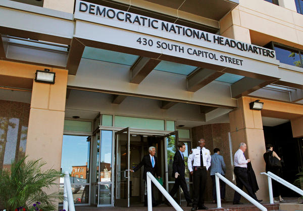 """People stand outside the Democratic National Committee headquarters in Washington, D.C., in June. DNC staffers said publication of leaked emails in July was a Russian ploy to support the candidacy of Donald Trump. But, says a Russian investigative journalist, """"I think it's not about Trump. It's all about Hillary Clinton."""""""
