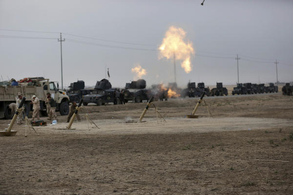 Iraqi special forces fire toward Islamic State positions near the village of Tob Zawa, outside Mosul, on Monday. Loudspeakers on the armored vehicles blared Iraqi patriotic music.