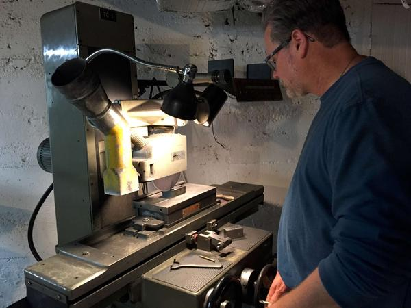 Phil McNeish works at a surface grinder in his basement, smoothing the surface of a plastic mold he fabricated. McNeish started his own company on the side as a way to make up income he says he's lost since NAFTA took effect. These days, he says every week he has to submit a bid competing against a manufacturer in China.