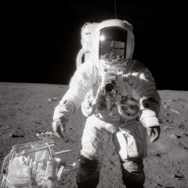 """Astronaut Alan Bean was photographed by Charles """"Pete"""" Conrad Jr., who is reflected in Bean's helmet visor, during the Apollo 12 moonwalk in 1969."""
