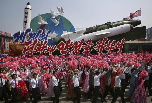 North Koreans wave as they march next to a float display of models of different missiles across Kim Il Sung Square in Pyongyang. The military parade celebrated the 105th birth anniversary of Kim Il Sung on April 15.