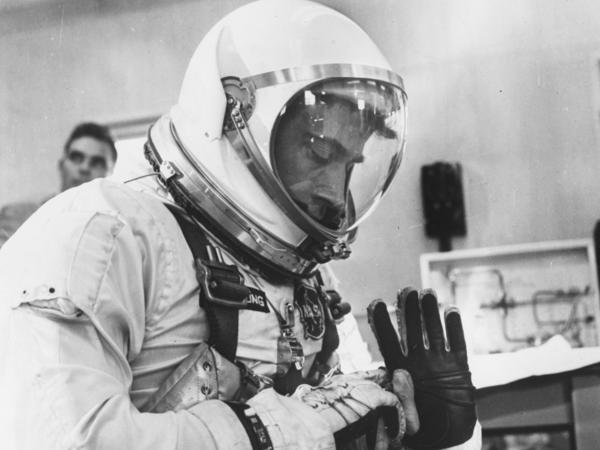 Astronaut John Young, co-pilot of NASA's Gemini 3, inspecting his space suit. He was the only astronaut to fly Gemini, Apollo and shuttle missions.