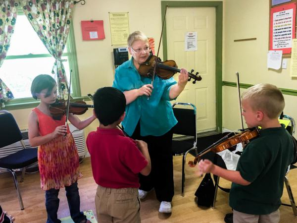 (From left to right) Mackenzie Stamper, Adrian Rodriguez and Luke Ryan attend weekly Suzuki violin lessons with instructor Sara Johnson, part of a training program called MILEStone, or Music Impacting Language Expertise.
