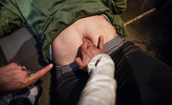 Keller measures the separation in a student's abdominal muscles using her fingers as a guide.