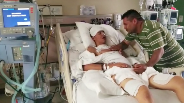 Brandon Martinez, 16, lies in a hospital bed while his father, Jose de Jesus Martinez, visits in the intensive care unit at North Central Baptist Hospital in San Antonio, Texas.