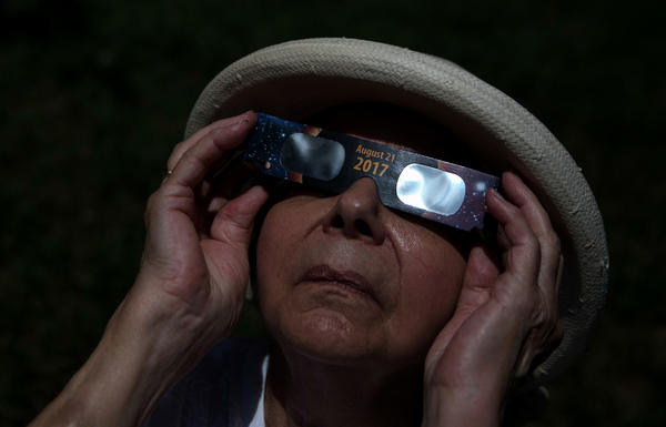 Margaret Julian looks through solar glasses to watch the total solar eclipse in midtown Atlanta.
