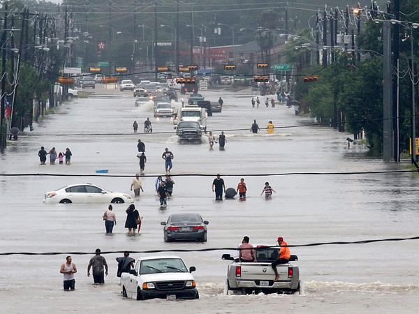 People walk through floodwaters on Telephone Road in Houston on Sunday after 2 feet of rain from Hurricane Harvey pummeled the Gulf Coast.