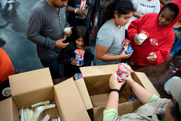 People taking shelter at the convention center pick up food. Around midday Monday, Gov. Greg Abbott activated the entire Texas National Guard to support communities coping with the flooding.