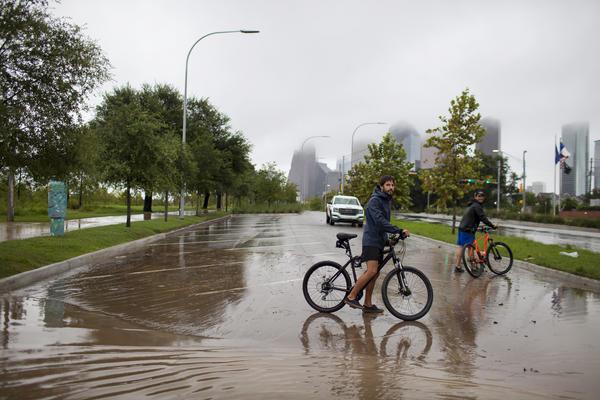 "Houston residents Julian Fernandez (left) and Simon Loscertales survey the flooding next to Buffalo Bayou Park in Houston. ""I am now a refugee,"" says Fernandez, whose neighborhood has flooded."
