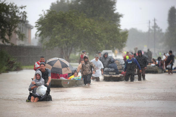 People are rescued from a flooded neighborhood after it was inundated with rain water.