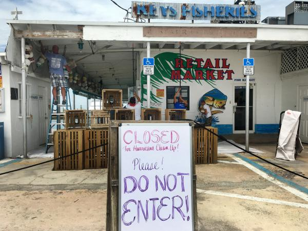Employees of Key Fisheries, a Marathon, Fla. fish market that was damaged by Hurricane Irma, clean up debris. Their business is closed to the public due to all the damage done by the storm.