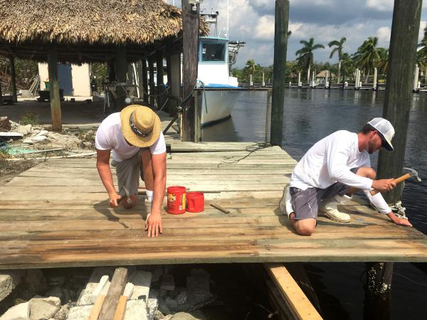 In Everglades City, Fla., crab fishermen Shane Reamao, left, and Dalton Daffin hurry to repair a commercial fishing dock that was destroyed during Hurricane Irma.