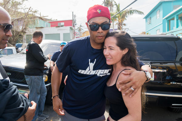 "Baseball Hall of Famer Roberto ""Robbie"" Alomar hugs resident Angela Magaña after delivering aid in La Perla. Alomar grew up in Puerto Rico."