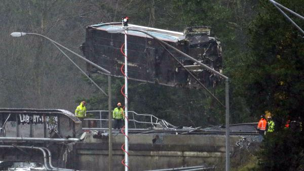 A damaged Amtrak train car is lowered from an overpass Tuesday at the scene of a train crash onto Interstate 5 a day earlier in DuPont, Wash. Federal investigators say they don't yet know why the Amtrak train was traveling 50 mph over the speed limit when it derailed. The rail cars will be taken to a nearby military base for closer analysis.