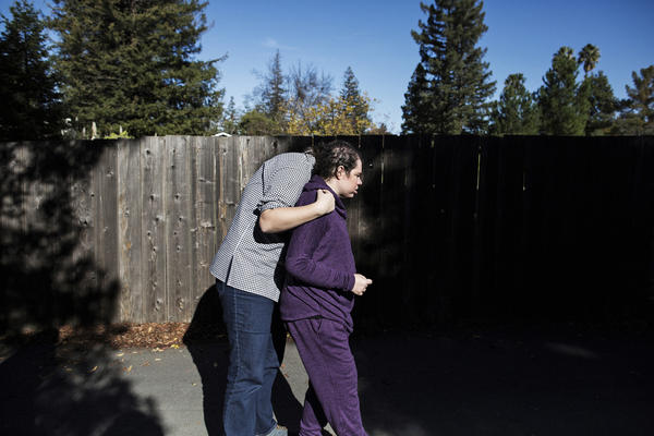 Natalie (right), who has a significant intellectual disability, is hugged by her part-time caretaker Mariah Hofstadter while being taken on a walk in the neighborhood.