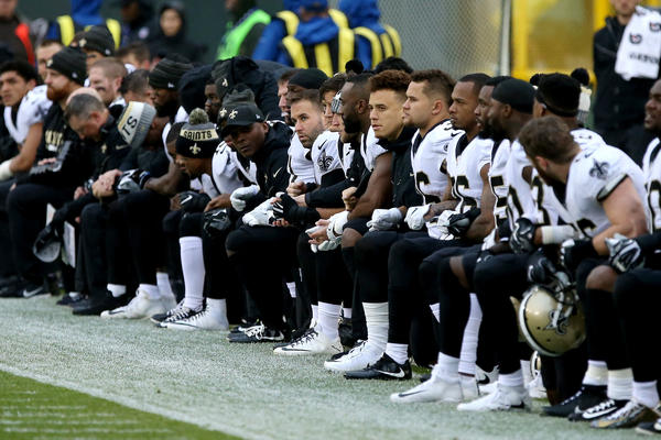 The New Orleans Saints kneel before the playing of the national anthem before the game against the Green Bay Packers at Lambeau Field on Oct. 22.