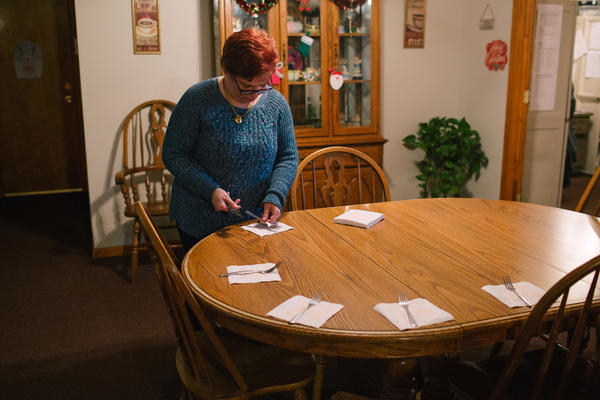 """Pauline helps set the table for dinner at her group home. """"I was scared the first day I went to the house,"""" she says, referring to the group home she currently lives in. """"I didn't know anyone."""" Since coming into the group home, Pauline says, she is happier."""