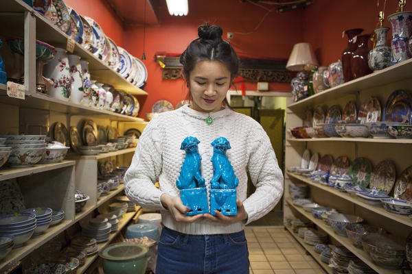 Mei Lum holds a pair of iconic Fu Dogs in a discontinued turquoise glaze from Jingdezhen, China. Mei put grad school plans on hold to take over her family's business.