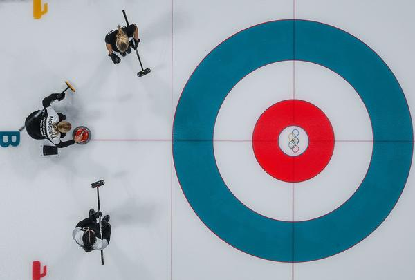 Russian athletes compete with Britain during the curling women's round-robin session on Feb. 14. Curling ice is textured with tiny dots called pebbles.