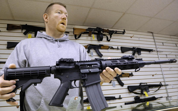 John Jackson, co-owner of Capitol City Arms Supply, with an AR-15 rifle for sale at his store in Springfield, Ill., in 2013. The semi-automatic rifle has been sold to the public since the 1960s and the NRA estimates that around 8 million AR-15s and related models are in circulation.