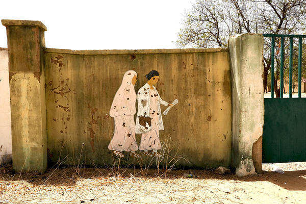 A mural showing a teacher leading a young girl to school is riddled with bullet holes after an attack by Boko Haram militants last month. They attacked the Dapchi Government Girls Science and Technology College in northeast Nigeria.