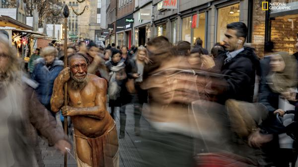 In Düsseldorf, Germany, a sculpture from the nearby Neanderthal Museum draws curiosity and recognition from passersby. The image is featured in the April issue of <em>National Geographic</em> magazine, a single-topic issue on the subject of race.